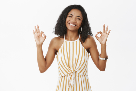 Everything be okay chill. Charming friendly-looking dark-skinned female with curly hairstyle smiling from happiness and joy tilting head showing okay or excellent gesture posing over grey wall Stock Photo
