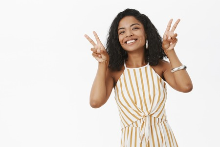 Girl bringing up happiness in life. Portrait of charming carefree African American woman with curly hairstyle smiling joyfully showing peace gestures and gazing at camera ambitious and delighted