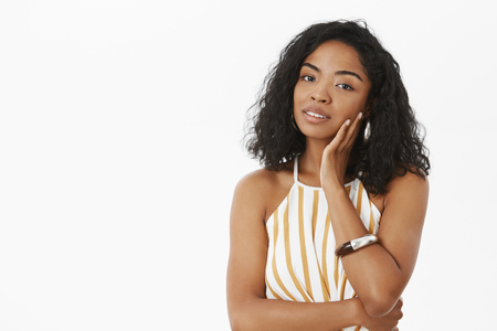 Make-up helos feel confidence. Portrait of feminine and sensual cute dark-skinned female touching face gently and gazing at camera with flirty look feeling beautiful taking care of skin Stock Photo