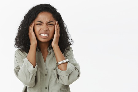 Head goes round from hangover. Portrait of displeased intense african american young woman with curly hair frowning clenching teeth from painful feeling touching temples suffering headache or migraine