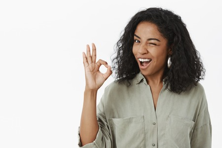 Okay I got it. Optimistic confident and carefree chill african american female coworker in grey stylish shirt winking like hinting assuring everything be great showing ok sign over gray background