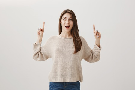 girl is excited seeing her name written in sky. Portrait of expressive beautiful woman with long hair looking and pointing up with index fingers, smiling, gasping from positive surprise over gray wall