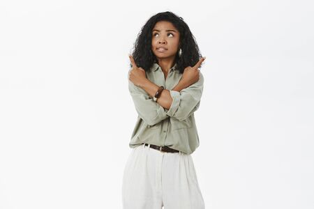 Concerned troubled attractive african american adult woman with curly hairstyle feeling unsure crossing arms on body and pointing in different direction looking at upper left corner making choice
