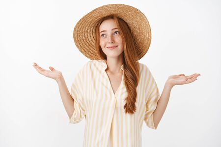 No big deal. Portrait of carefree optimistic charming kind female with ginger hair and freckles in cute straw hat and yellow blouse making shoulder shrugg with hands spread and innocent look