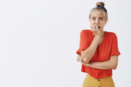 Studio shot of afraid nervous woman about to panic standing in vintage dotted blouse biting fingernails and staring concerned and worried at camera feeling anxious over gray background