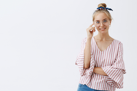 Indoor shot of good-looking smart and creative female entrepreneur in stylish striped v-neck blouse and glasses, touching rim and gazing with friendly look at camera over gray background