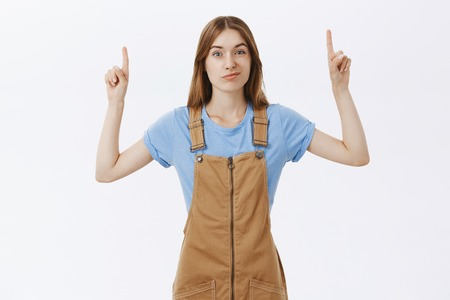 Doubtful and hesitant cute unimpressed girlfriend in brown overalls over t-shirt raising hands pointing up and smirking with displeased suspicious expression giving negative feedback over white wall Stockfoto