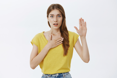 I swear telling truth. Portrait of worried and nervous cute timid young girl holding palm on chest and raising hand swearing to be honest facing judge or trial standing against gray background
