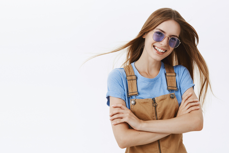 Beauty, style and fashion concept. Charming outgoing attractive young woman in brown overalls and sunglasses tilting head smiling happily crossing hands over chest in confident and self-assured pose