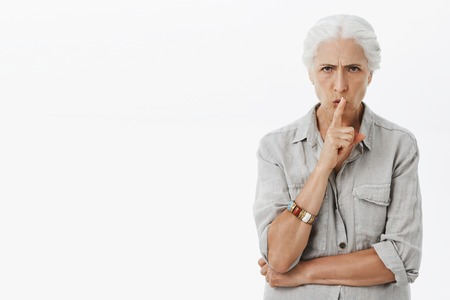 Portrait of serious-looking dissatisfied and angry energized elderly woman with white hair frowning shushing at camera with index finger over mouth Stock Photo