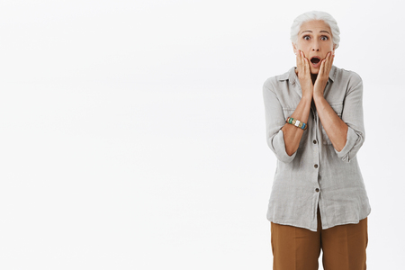 Portrait of shocked and excited senior lady with white hair dropping jaw touching face with both palms reacting on shocking and terrifying scene looking worried over gray background