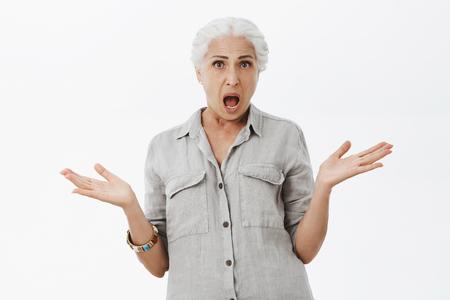Studio-opname van een verwarde en ontevreden geschokte oudere moeder met wit haar die haar schouders ophaalt en de handpalmen opzij steekt, terwijl ze ruzie maakt met een kind dat geen idee heeft waarom hij zo ondeugend wordt over een grijze muur