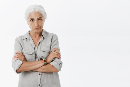 Madre anciana enojada disgustada con cabello gris mirando por debajo de la frente con expresión irritada frunciendo los labios cruzando los brazos sobre el pecho regañando a la nieta