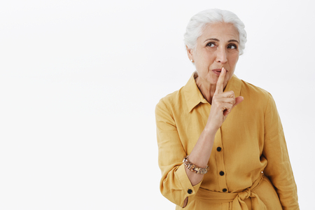 Waist-up shot of wise and creative charismatic elderly mother with white hair smiling intriguing and myseteriously saying shh making surprise showing shush gesture with index finger over mouth Stock Photo