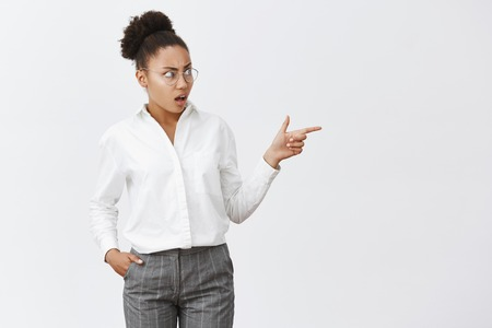 Damn, girl, what you wearing. Portrait of displeased intense and confused female coworker with dark skin in glasses and suit, pointing and staring right with puzzled and dislike expression