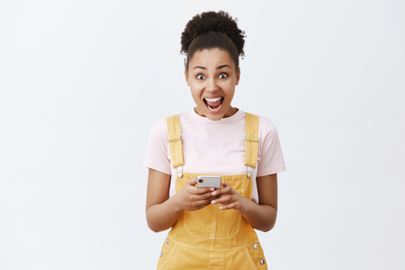 Womans creaming from emotions, receiving invitation to famous party. Portrait of surprised and amazed good-looking dark-skinned girl in yellow overalls, yelling at camera and holding smartphone