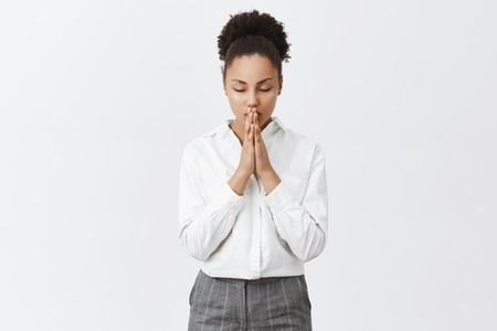 Relaxed and focused good-looking dark-skinned female entrepreneur calming down while holding palms together, praying or hoping, being believer in miracles Imagens