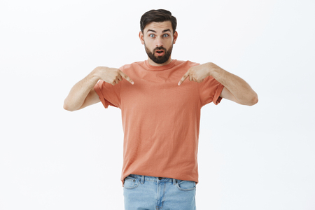 Indoor shot of surprised intense and confused charming caucasian adult guy with beard opening mouth, raising eyebrows unsure and surprised pointing at himself with raised index finger over gray wall