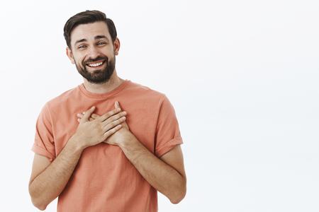 Happy delighted and grateful adult european man with beard in pink t-shirt holding palms on heart and smiling thankful receiving compliments or gift posing cheerful over gray background