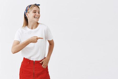 Studio shot of good-lookng carefree female shop assistant laughing and talking casually with coworkers, holding hand in pocket, looking and pointing right with broad smile over gray background Stock fotó