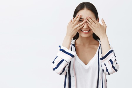 Portrait of intrigued playful charming woman in striped blouse, covering eyes with palms and peeking through fingers, smiling broadly at camera, waiting surprise