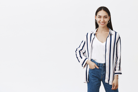 Indoor shot of creative good-looking stylish designer in striped blouse and stylish jeans, holding hand in pocket while smiling broadly at camera, standing in relaxed and confident pose over gray wall