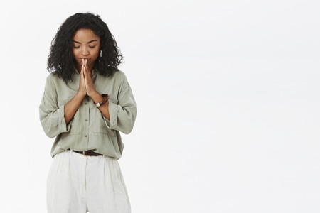 Portrait of faithful dark-skinned good-looking female with curly hairstyle bending head down closing eyes standing peaceful and relaxed with hands in pray hoping everything be alright over gray wall Stok Fotoğraf