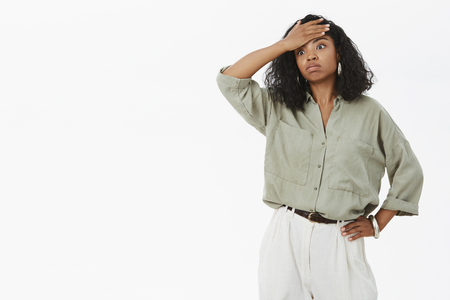 Portrait of fed up tensed and exhausted cute dark-skinned businesswoman in blouse and pants holding hand on waist exhaling and wiping sweat from forehead