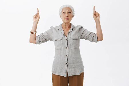 Studio shot of concerned hesitating and uncertain perplexed old woman in shirt and pants looking and pointing up