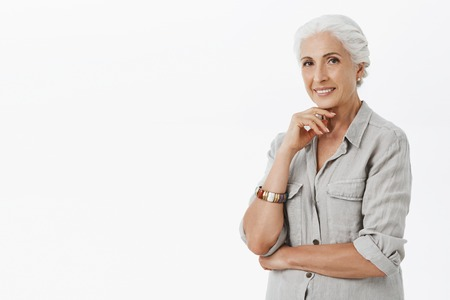 Waist-up shot of charming old lady with grey hair in casual shirt and bracelet holding finger above chin standing half-turned interested and curious listening carefully to intiguing concept, smiling
