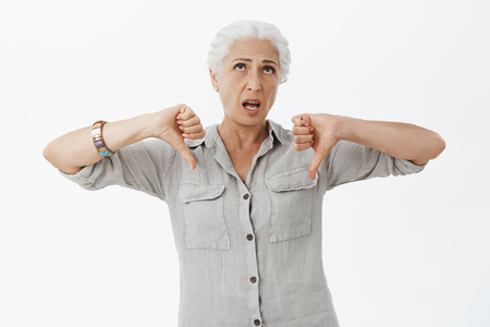 Energized unimpressed emotive elderly mother with grey hair in casual shirt rolling eyes up from boredom showing thumbs down in dislike gesture over grey wall