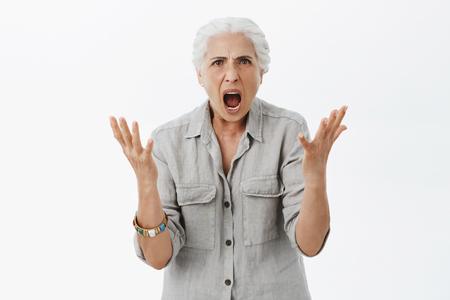 Porträt einer unzufriedenen, wütenden und wütenden Großmutter mit weißem Haar in lässigem Hemd, die in ahnungsloser Geste die Handflächen hebt und die Hände schüttelt und die Stirn runzelt, während sie sich streitet