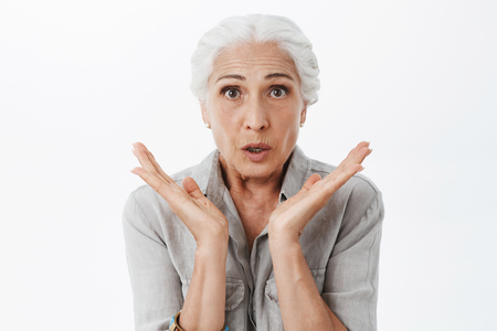 Waist-up shot of anxious and surprised kind grandmother feeling worried and amazed holding palms near face looking concerned and interested