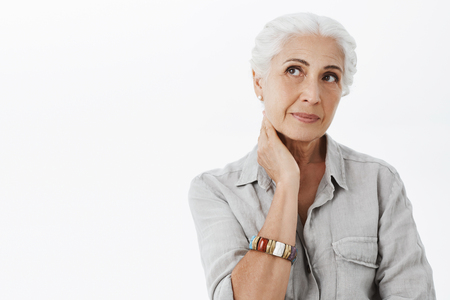 Waist-up shot of nostalgic and thoughtful wise cute senior woman with white hair touching neck gazing at upper left corner having health problems feeling ache in back posing over gray background