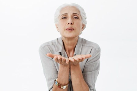 Waist-up shot of charming elderly wife with grey hair in shirt bending towards camera holding palms near folded lips sending air kiss at camera blowing mwah to husband still loving him passionately Stock Photo