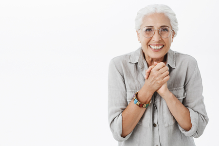 shot of excited enthusiastic and happy elderly woman in glasses and shirt clenching palms together over chest stooping shoulders from joy and impatience smiling being grateful and thankful