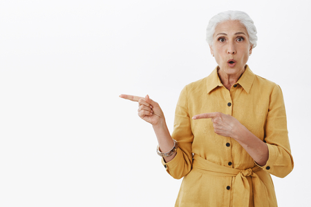 Studio shot of questioned and interested stylish grandmother with white hair in yellow trendy coat folding lips from curiosity pointing left with index fingers asking question over grey wall Фото со стока