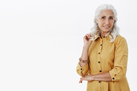 Portrait of fashionable elegant and confident old woman with grey hair in yellow trendy coat holding hand crossed on chest and raised arm near face posing with happy relaxed smile over white wall Stock Photo