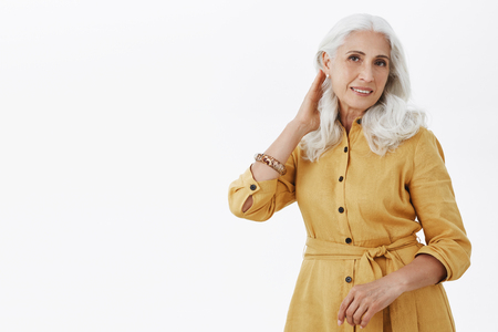 Waist-up shot of confident feminine and elegant old woman with white hair in stylish yellow trench coat touching haircut and gazing delighted and romantic at camera feeling self-assured in own beauty