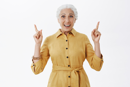 Waist-up shot of amazed and excited happy charming european senior lady in stylish trench coat raising arms pointing up and smiling with amusement and joy posing delighted over gray background Foto de archivo