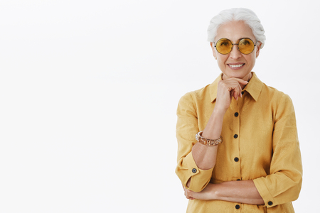 Stylish fashionable and happy energized senior woman with grey hair in trendy yellow sunglasses and coat holding hand on chin and smiling with delight creating new fashion line from elder people Фото со стока