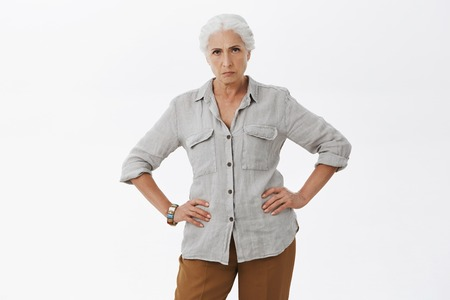 Explain you behavior young man. Portrait of strict and disappointed mad granny standing in displeased pose with hands in waist frowning staring angry at camera being dissatisfied posing over gray wall