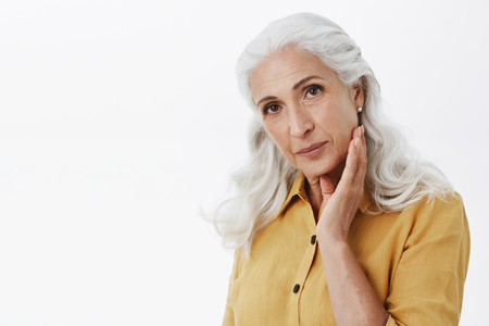 Confident and feminine elegant elderly woman with long white hair in stylish yellow trench coat touching face gently and gazing at camera satisfied with how skin looks, taking care of appearance