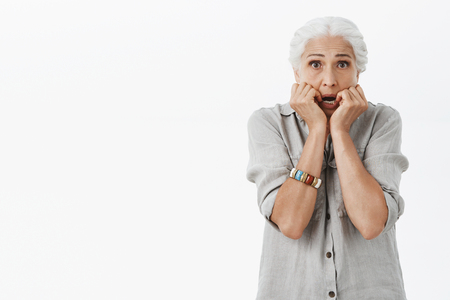 Waist-up shot of scared and concerned old lonely lady feeling unsafe and trembling from fear holding palms near mouth stooping standing worried and frightened against gray background