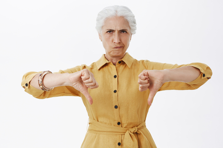 Waist-up shot of gloomy serious-looking, dissatisfied senior female customer in stylish yellow trench coat showing thumbs down smirking from dislike, disapproving unimpressive product over gray wall Stok Fotoğraf