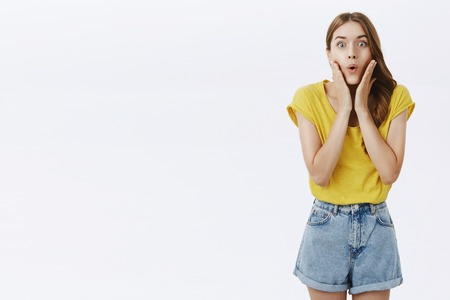 Intrigued girlfriend listening carefully amazing rumors. Amazed interested charming adult woman in yellow t-shirt and shorts folding lips holding palms on cheeks from curiosity and excitement Stock Photo