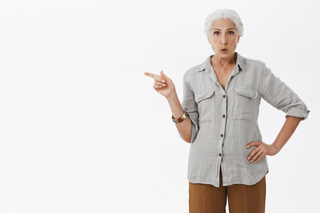 Intrigued granny with gray hair in casual loose shirt holding hand on waist pointing left curiously folding lips from surprise and interest asking question about promotion over white background