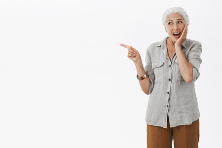 Portrait of amused and excited happy charming senior woman with white hair in casual shirt touching cheek gently from surprise pointing and looking left with delight smile over gray background