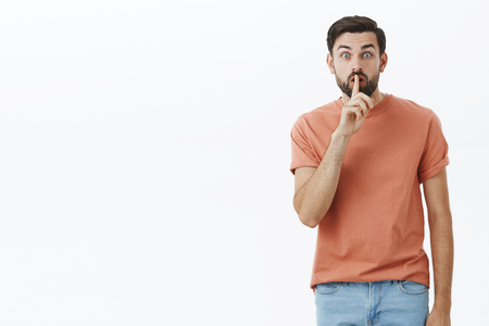 Guy telling friend keep mouth shut and save secret. Portrait of excited and intense good-looking adult male with beard saying shh making shush gesture with index finger over mouth against gray wall