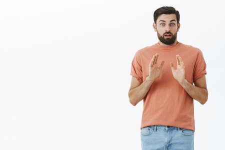 Worried and nervous boyfriend afraid of responsibilities wanting take step back with relationship raising palms in stop and rejection gesture looking anxious at camera over gray wall